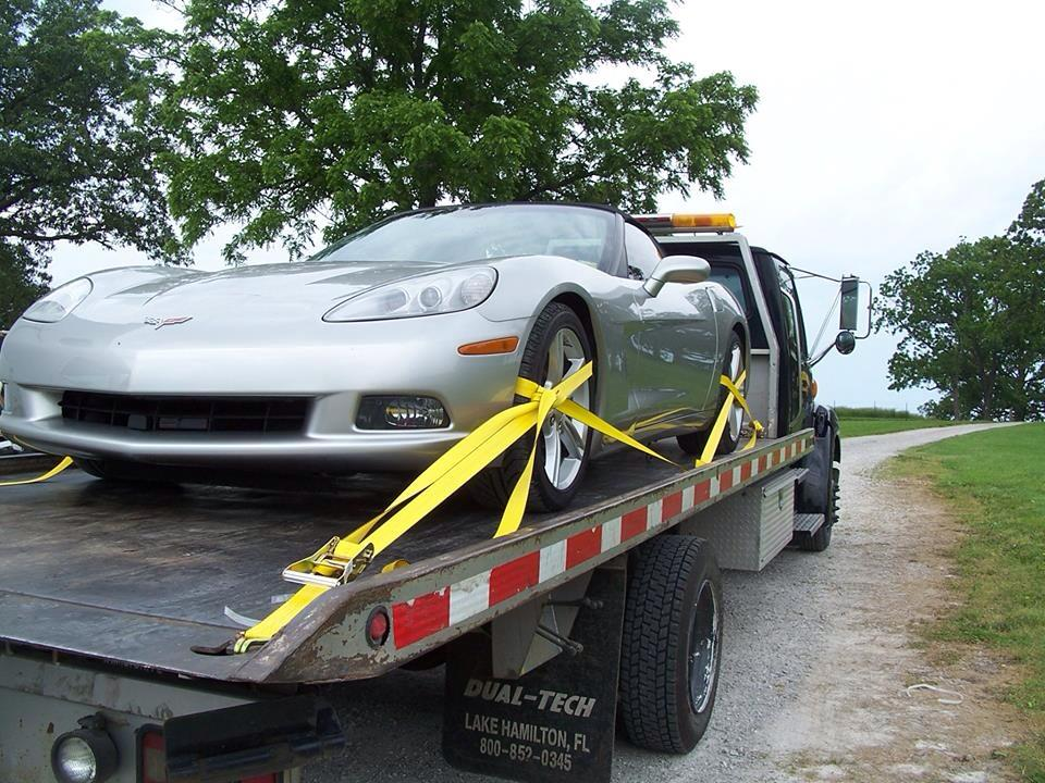 flat bed tow truck hauling a corvette   affordable towing